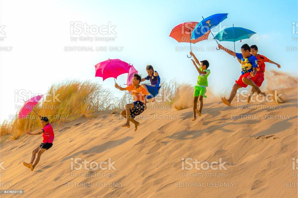 Kids jump off sand dune with umbrellas. stock photo