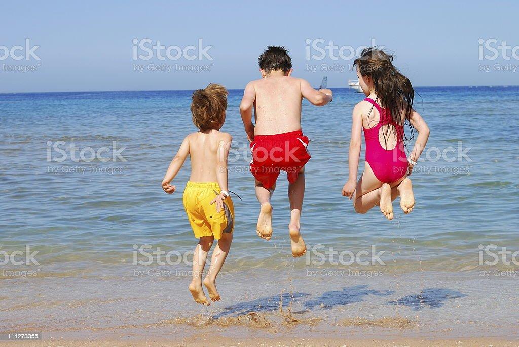 kids jumping at the beach royalty-free stock photo