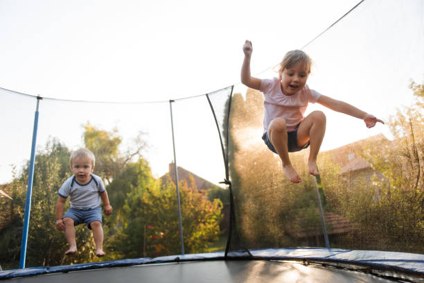 Kids jumping high on trampoline Siblings having fun together outside on trampoline real life stock pictures, royalty-free photos & images