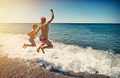 Brother and sister are having fun in sea.  Kids are jumping over a wave into the sea. They are caught mid air flying into the sea fun.\n\n