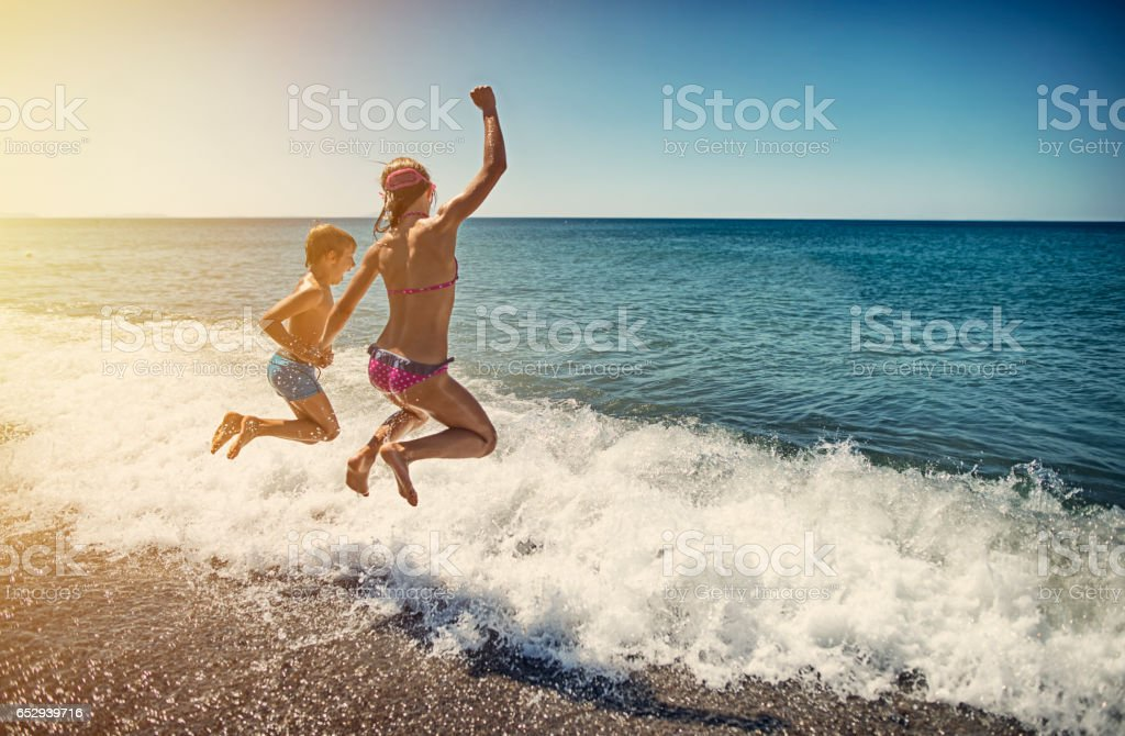 Kids jumping into sea stock photo