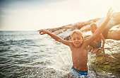 Two little brothers aged 7 are having fun in sea.  Kids are jumping into the sea from big stones. Sunny summer day in Tuscany, Italy.