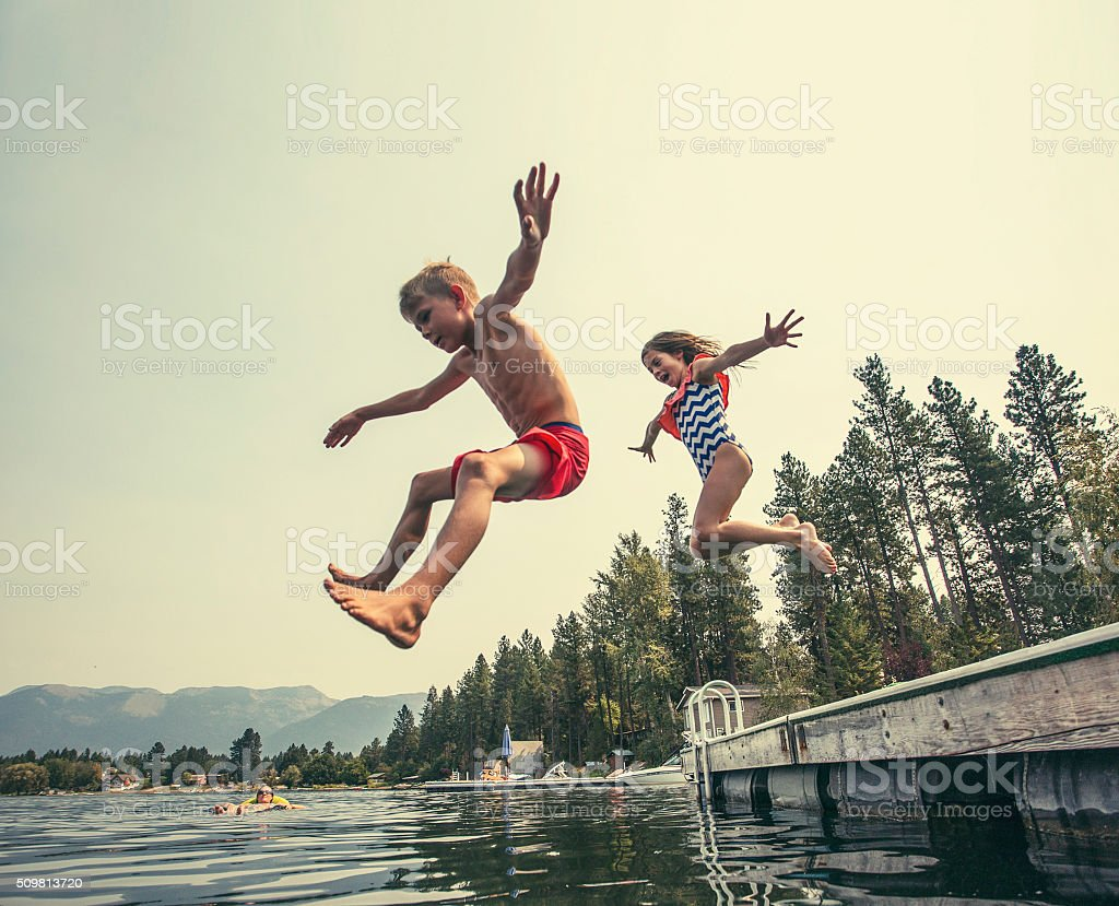Kids jumping off the dock into a beautiful mountain lake royalty-free stock photo