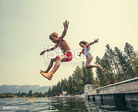 509813720 istock photo Kids jumping off the dock into a beautiful mountain lake 509813720