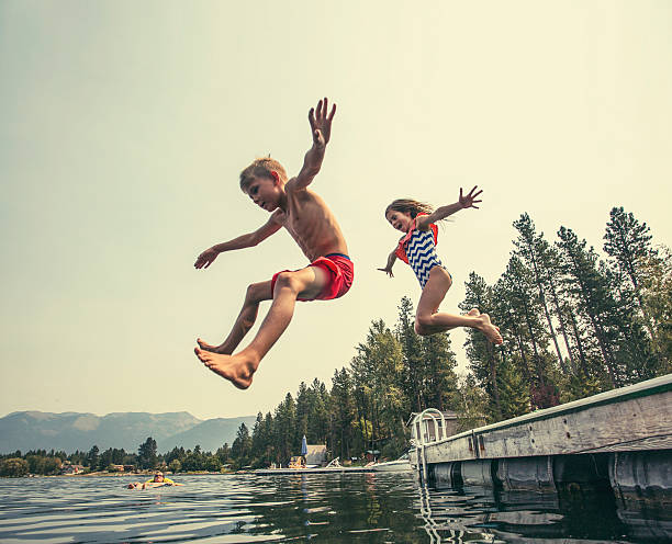 Kids jumping off the dock into a beautiful mountain lake stock photo