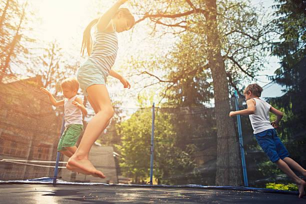 salto sobre trampolín al jardín para niños - trampolín artículos deportivos fotografías e imágenes de stock