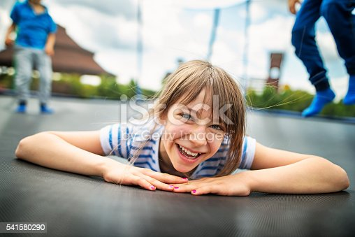 Little boys aged 6 and the girl aged 10 having fun on trampoline.