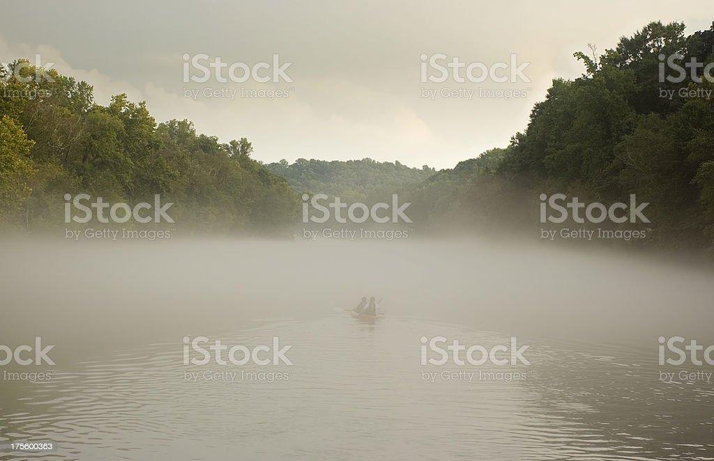 Kids kayaking in fog royalty-free stock photo