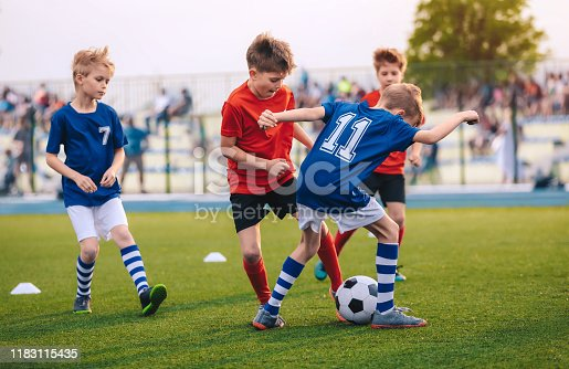 Kids Kicking Football Ball. Boys Play Soccer on Grass Field. Spectators Parents in the Background. Youth Players kicking Soccer Match on grass Stadium. Youth Football Tournament