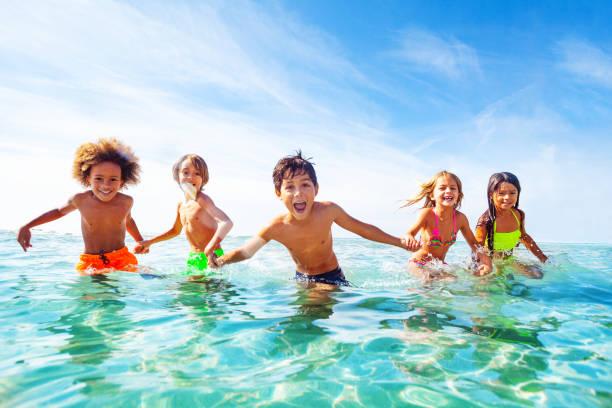 Kinder lachen und spielen im Wasser am Meer – Foto