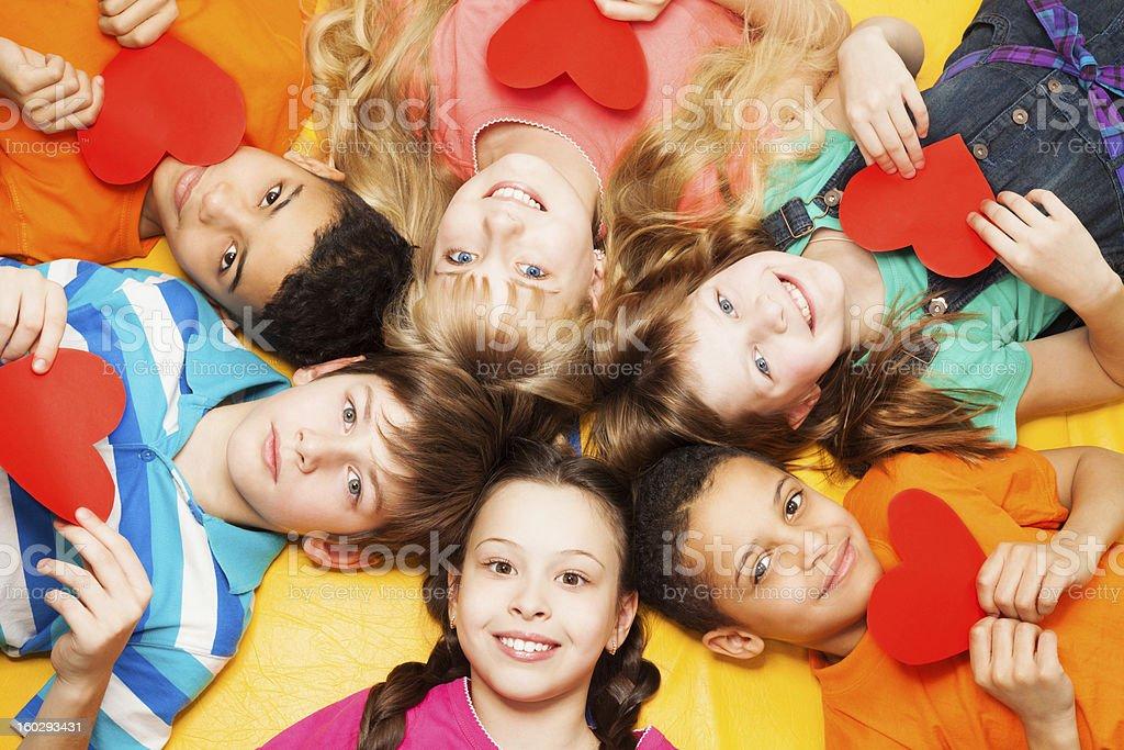 Los niños pueden sentar en un círculo con el corazón en sus manos - foto de stock