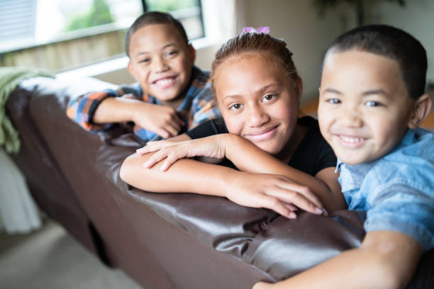 kids leaning at sofa and looking at camera. - maori stock photos and pictures