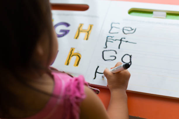 kids learning how to write the abc's at home. stock photo