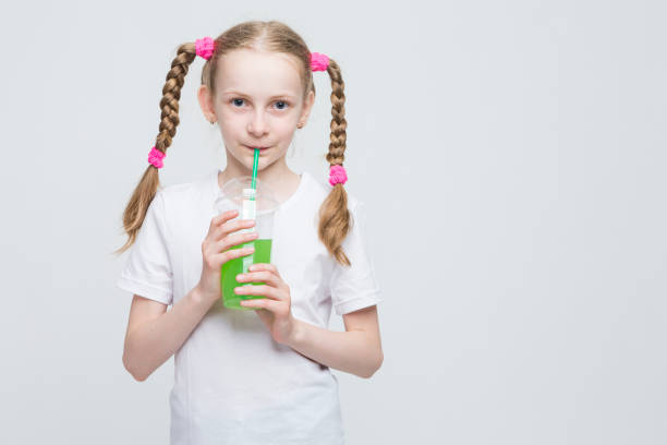 Kids Lifestyle Concepts. Portrait of Pretty Smiling Caucasian Blond Girl With Long Pigtails Holding Cup and Drinking Green Juice Through Straw. Horizontal Image Composition