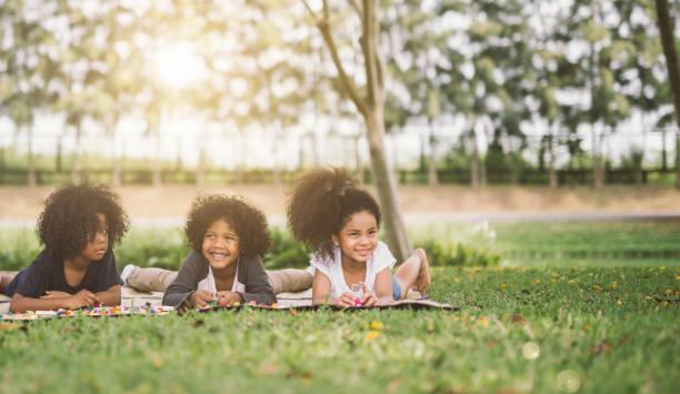 kinder kleine freunde, die verlegung auf dem rasen - kinder picknick spiele stock-fotos und bilder