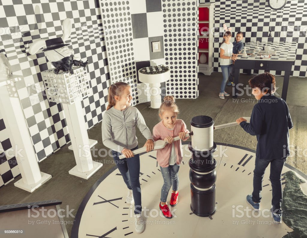 kids look for a way out in quest room in chess style stock photo