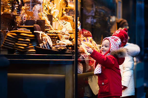 kids looking at candy and pastry on christmas market - weihnachtsfeier münchen stock-fotos und bilder