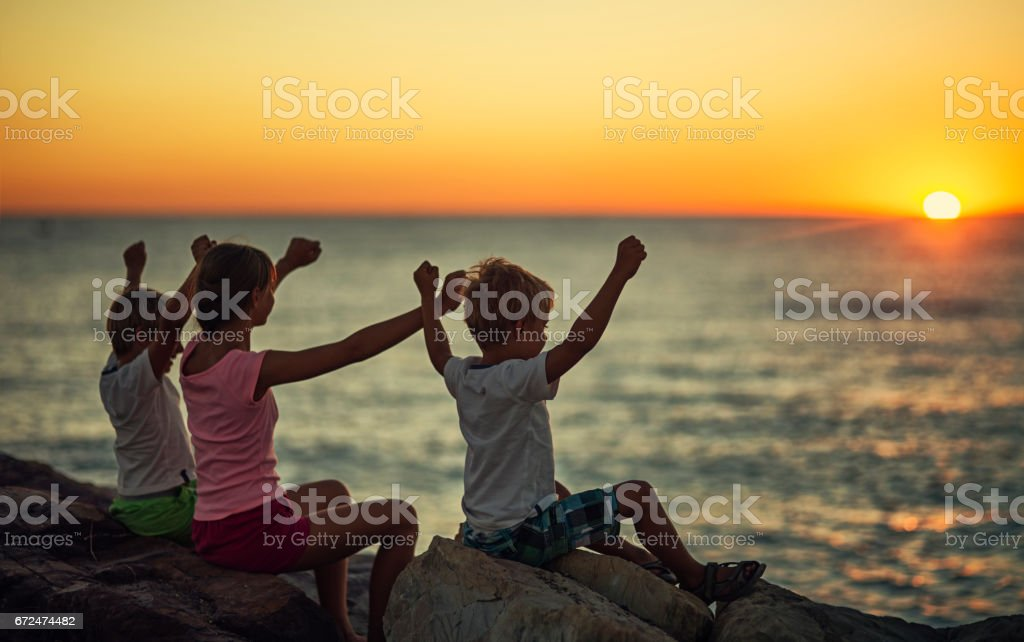 Kids looking at the sunset over the Italian sea. stock photo