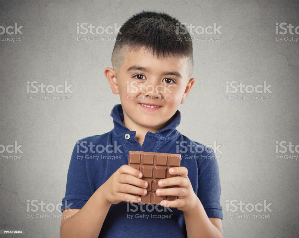 Kids love sweets. Portrait happy little boy eating whole bar of chocolate stock photo