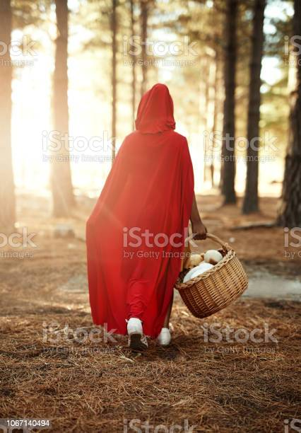 Rear view shot of a little girl in a red cape walking in the woods with a basket