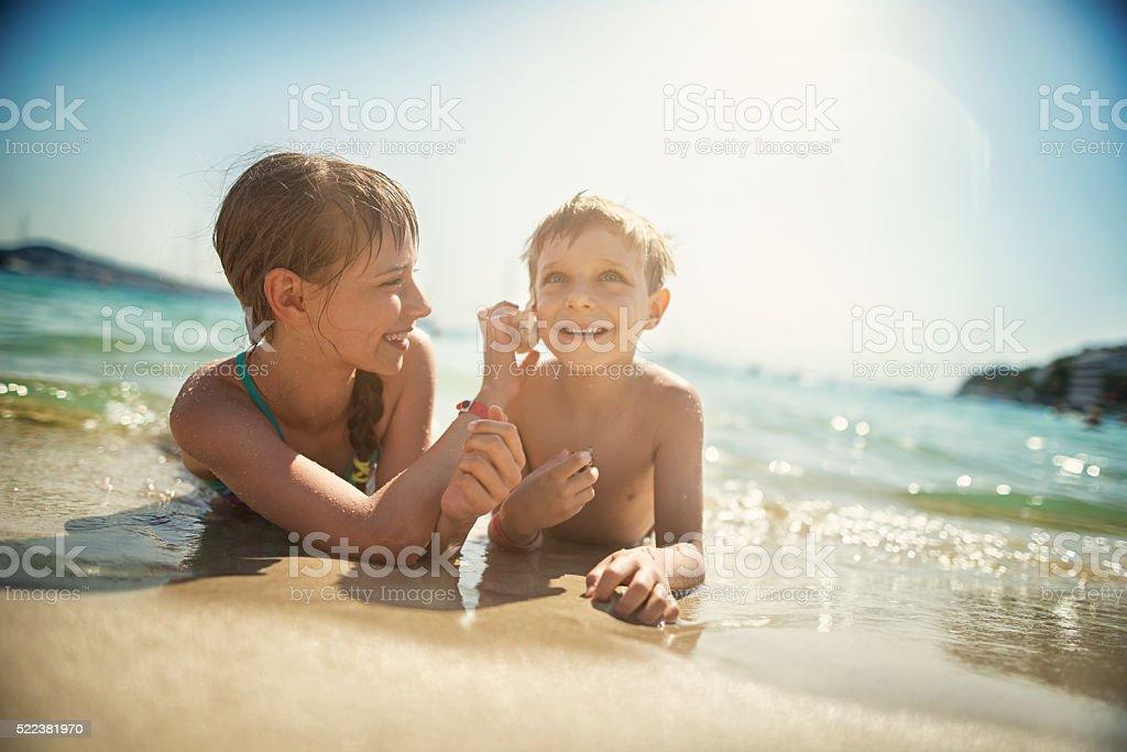 Kids lying on beach listening to sea shells stok fotoğrafı