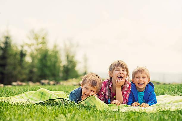 kinder auf dem bauch liegen auf gras-decke genießen lustiger frühlings-picknick. - kinder picknick spiele stock-fotos und bilder