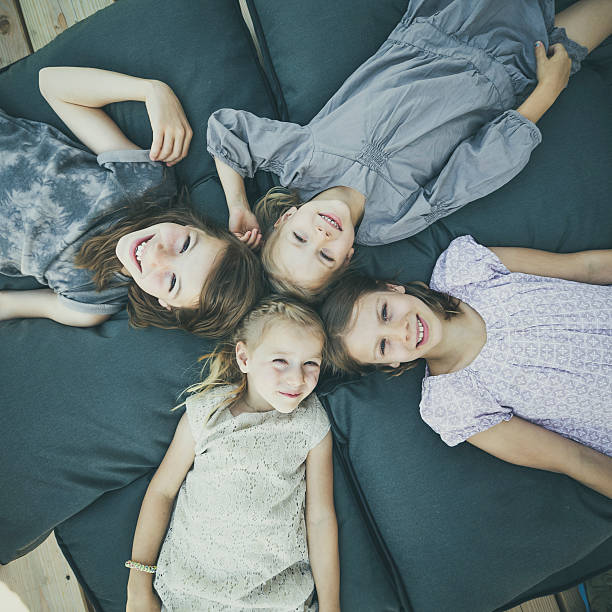 kids lying on pillows stock photo