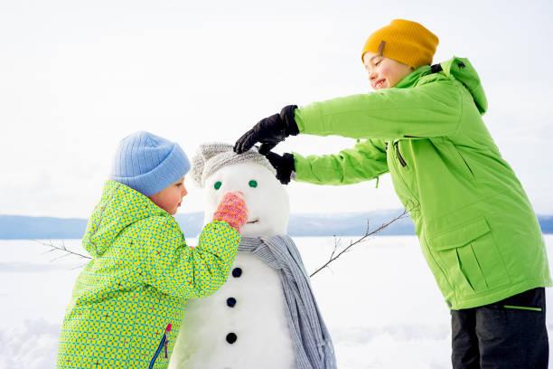 kids making a snowman - schneemann bauen stock-fotos und bilder