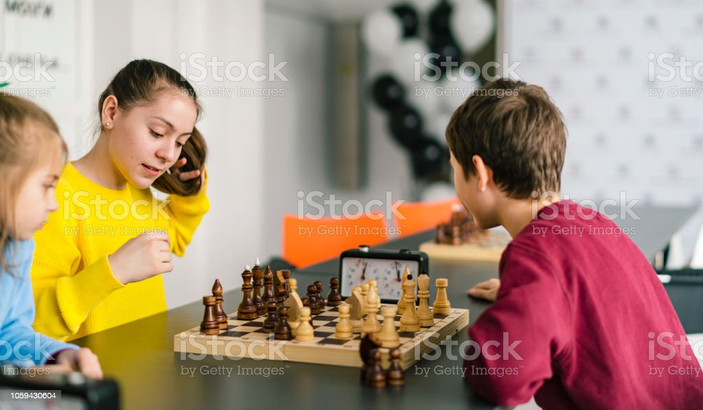 Kids of different ages, boys and girls, playing chess on the tournament in the chess club stock photo