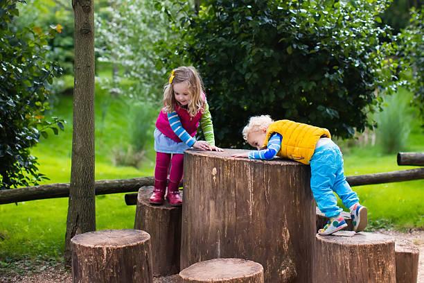 kids on a playground in a park - kinder picknick spiele stock-fotos und bilder