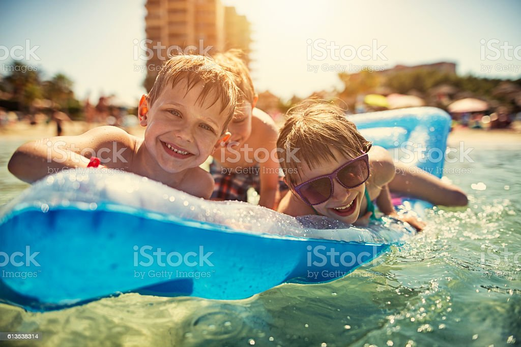 Kids on air mattress playing and laughing at sea stock photo
