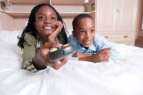Kids on Bed Watching TV stock photo