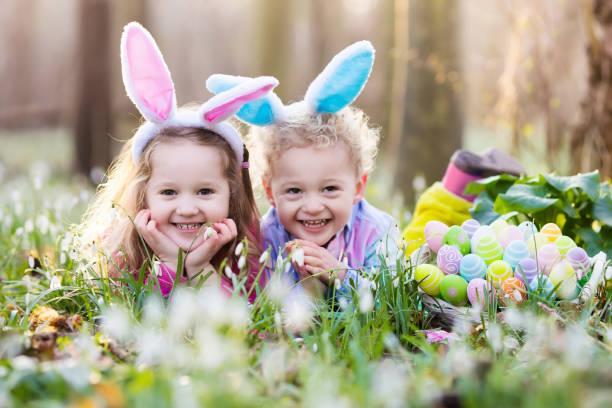 bambini su uovo di pasqua caccia in fioritura primavera giardino - buona pasqua in tedesco foto e immagini stock
