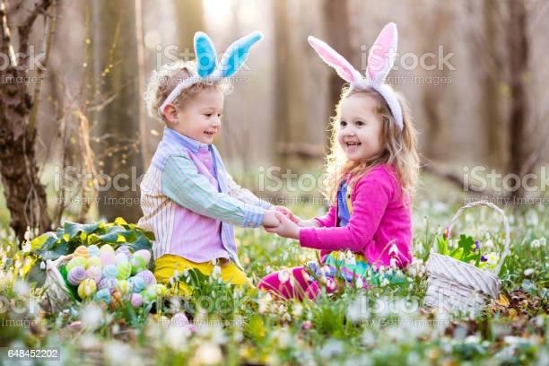 Kids on easter egg hunt in blooming spring garden picture id648452202?b=1&k=6&m=648452202&s=612x612&h=hmhpyshdwgahhdabuhrbdkaz76bhn0udq9f6 4mx yg=