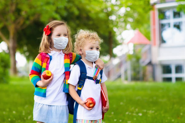 Kids on first school day in face mask stock photo