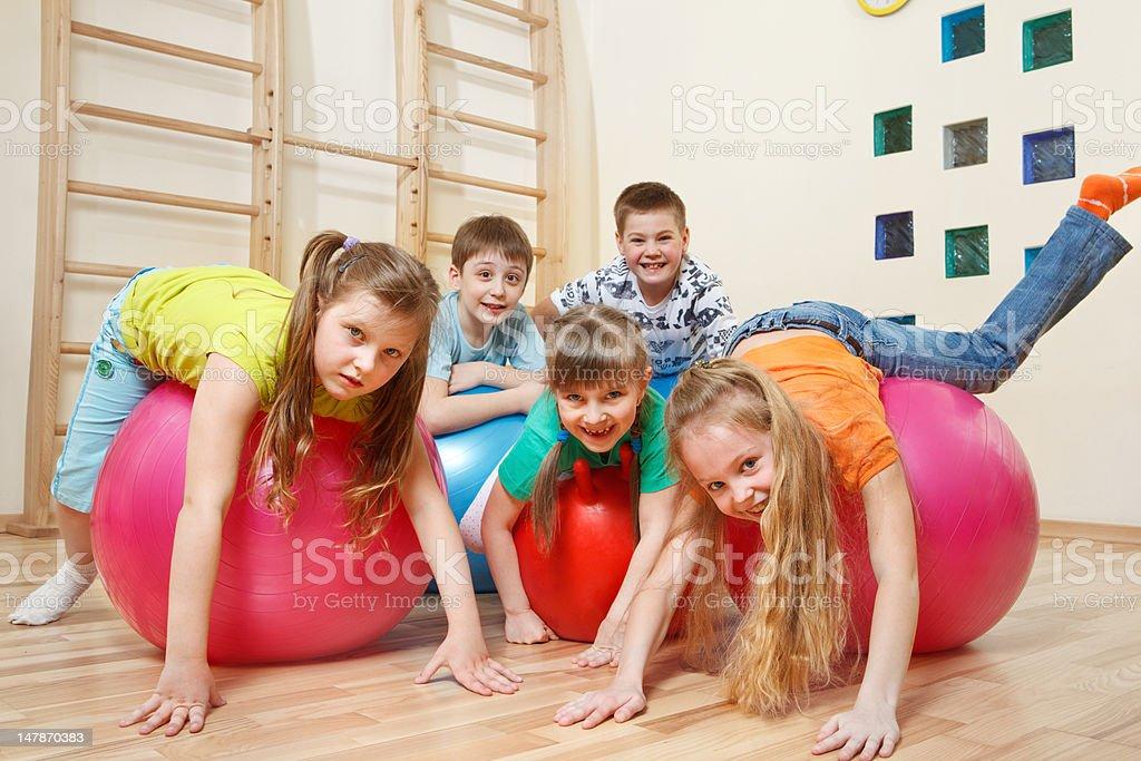 Kids on  gymnastic balls stock photo