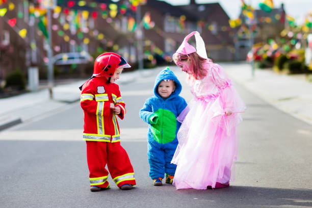 Kids on Halloween trick or treat. Kids on Halloween trick or treat. Children in Halloween costumes with candy bags walking in decorated city neighborhood trick or treating. Baby and preschooler celebrating carnival wearing costume. carnival children stock pictures, royalty-free photos & images
