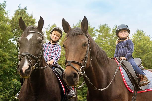 niños en los caballos hermano y hermana cabalgatas - equitación fotografías e imágenes de stock