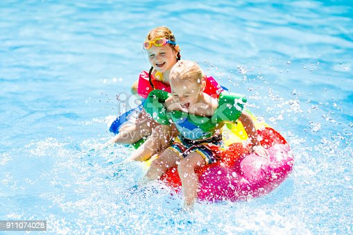 istock Kids on inflatable float in swimming pool. 911074028