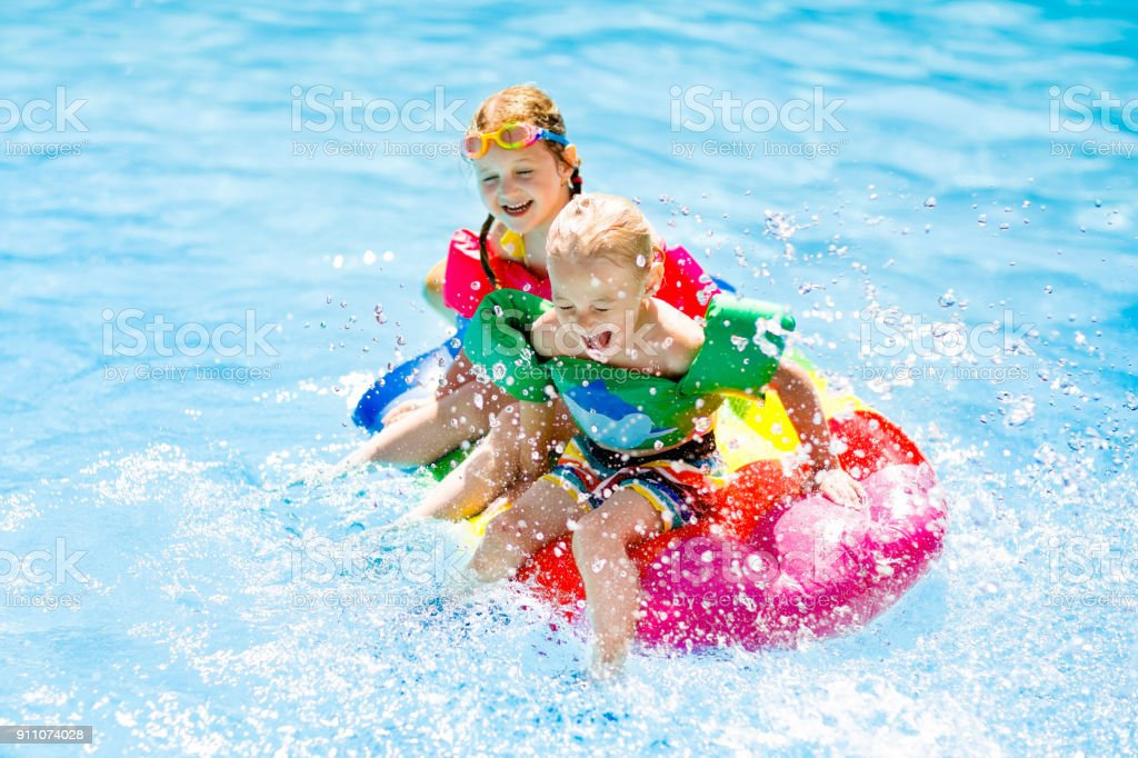 Kids on inflatable float in swimming pool. stock photo
