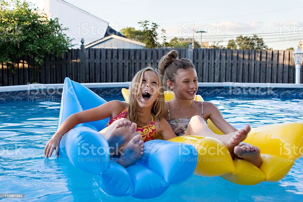 Kids on inflatables in swimming pool stock photo