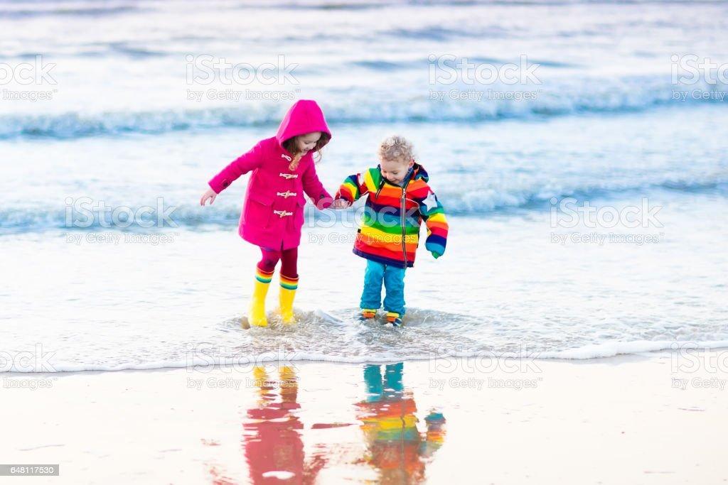 Kinderen op Noordzeestrand in de winter foto
