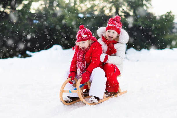 Kids on sleigh. Children sled. Winter snow fun. Little girl and boy enjoy a sleigh ride. Child sledding. Toddler kid riding a sledge. Children play outdoors in snow. Kids sled in Alps mountains in winter. Outdoor fun for family Christmas vacation. sleigh stock pictures, royalty-free photos & images