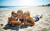 Kids lying on beach and using tablet to talk to grandmother.\nNikon D850