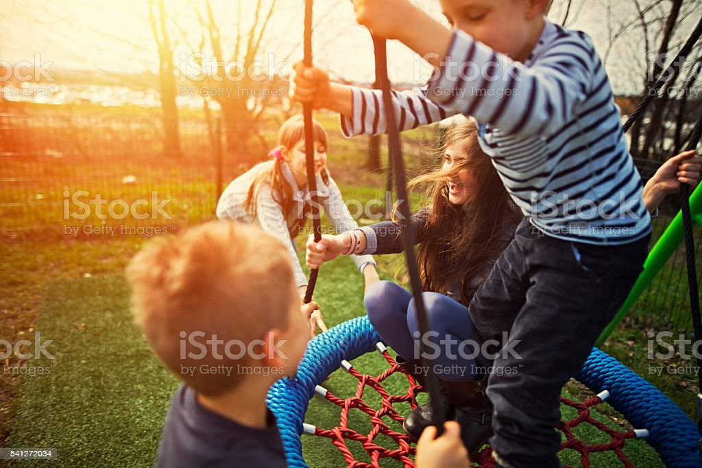 Kids on the playground, swinging on a big swing stock photo
