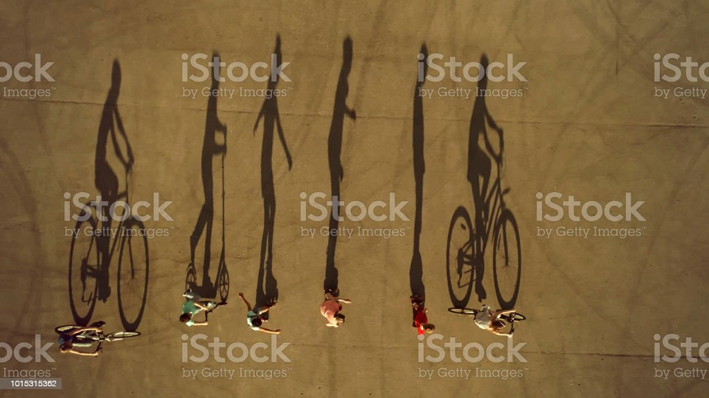 Kids on Wheels Cast Long Shadows. Cycling, Roller Skating and Scootering stock photo