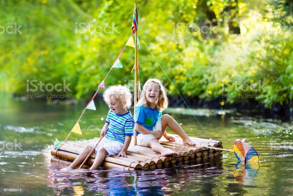 Kids on wooden raft royalty-free stock photo