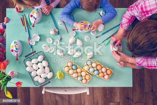 istock Kids Painting Easter Eggs 645980914