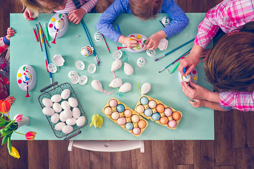 Cute little kids having fun with coloring Easter eggs with various colors.