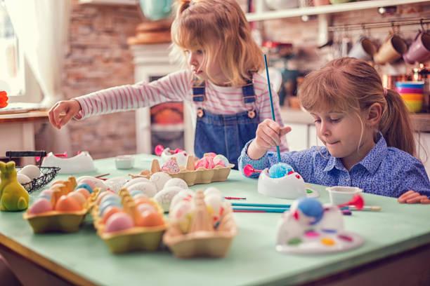 kids painting easter eggs - buona pasqua in tedesco foto e immagini stock